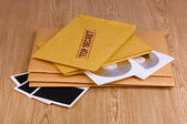 Envelopes with top secret stamp with photo papers and CD disks on wooden background — Stock Photo