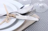 Brancos pratos vazios, garfo e faca, amarrado com uma fita e óculos numa toalha de mesa cinza — Fotografia Stock