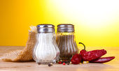 Salt and pepper mills and spices on wooden table on yellow background — Stock Photo