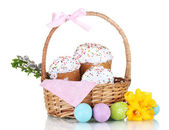 Beautiful Easter cakes in basket, colorful eggs and flowers isolated on white — Stock Photo