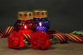 Lanterne de mémoire avec des bougies, des oeillets rouges et ruban de saint-georges sur une table en bois sur fond gris — Photo