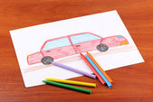 Children's drawing of red car and pencils on wooden background — Foto Stock
