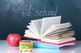 Composition of books, stationery and an apple on the teacher's desk in the background of the blackboard. Back to school. — Stock Photo