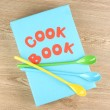 Cookbook and kitchenware on wooden background — Stock Photo #10259310