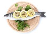 Pesce fresco con limone, prezzemolo e pepe sul tagliere di legno isolato su bianco — Foto Stock
