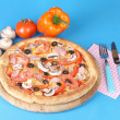 Aromatic pizza with vegetablesand mushrooms on blue background - Stock Photo