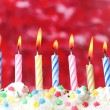 Beautiful birthday candles  on red background - Stock Photo