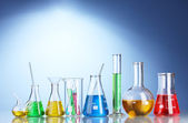 Different laboratory glassware with color liquid and with reflection on blue background — Stock Photo
