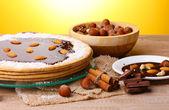 Dort na skleněná kostka a ořechy na dřevěný stůl na žlutém podkladu — Stock fotografie