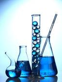 пробирки с синей жидкостью на синем фоне — Стоковое фото