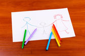 Children's drawing of family and pencils on wooden background — Stok fotoğraf