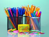 Colored holders for office supplies with them on bright background — Stock Photo