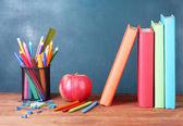 Skład książki, artykuły papiernicze i jabłko na biurku nauczyciela w tle tablicy — Zdjęcie stockowe