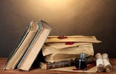 Old books, scrolls, ink pen and inkwell on wooden table on brown background — Stock Photo