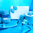 Beautiful gifts, babys bootees, blank postcard and dummy on blue silk — Stock Photo #10341545