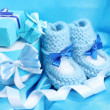 Beautiful gifts and babys bootees on blue silk — Stock Photo