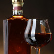 Glass of brandy and bottle on brown background — Stock Photo #10341745