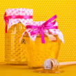 Jars of honey and wooden drizzler on yellow honeycomb background — Stock Photo #10346979