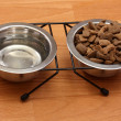 Dry dog food and water in metal bowls on the floor - Stock Photo