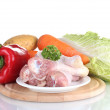Fresh vegetables with raw chicken drumsticks on cutting board isolated on white — Stock Photo #10347364