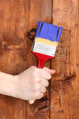 Painting wooden fence with yellow paint — Stock Photo