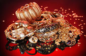 Beautiful golden jewelry on red background — Stock Photo