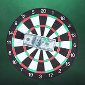 Dollar on bulls eye. Darts on colorful background — Stock Photo
