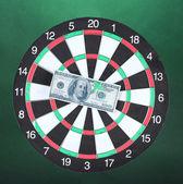 Dollar on bulls eye. Darts on colorful background — Stock Photo