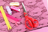 Scissors and bright threads with zips on fabric — Stock Photo