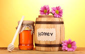 Sweet honey in barrel and jar with drizzler on wooden table on yellow background — Stock Photo