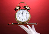 Hand in glove holding silver tray with alarm clock on red background — Stok fotoğraf