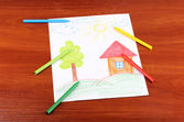 Childrens drawing of house and pencils on wooden background — Stock Photo