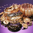 Beautiful golden jewelry on purple background - Foto Stock