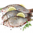 Fresh fishes with lemon, parsley and spice isolated on white - Stock Photo