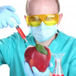Stock Photo: Scientist injecting GMO into apple