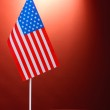 American flag on the stand and book on wooden table on red background — Stock Photo