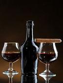 Láhev a glasss brandy a doutník na hnědé pozadí — Stock fotografie