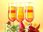 Fruit jelly in glasses and fruits on yellow background — Stock Photo