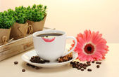 Cup of coffee with lipstick mark and gerbera beans, cinnamon sticks on wooden table — Stock Photo