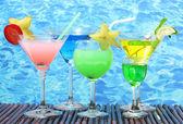 Copas de cócteles en mesa sobre fondo azul del mar — Foto de Stock