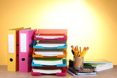 Bright paper trays and stationery on wooden table on yellow background — Foto de Stock