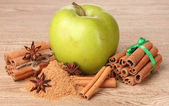 Bastoncini di cannella, mela verde e anice sul tavolo di legno — Foto Stock