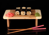 Tasty rolls served on wooden plate isolated on black — Stock Photo