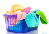 Plastic basket with bright towels isolated on white — Stock Photo
