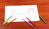 Aile ve kalemleri ahşap arka plan üzerinde çizim çocuk — Stok fotoğraf