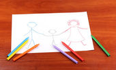 Childrens drawing of family and pencils on wooden background — Stock Photo