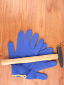Hammer and gloves on wooden background — Stock Photo