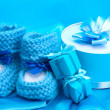 Beautiful gifts and babys bootees on blue silk — Stock Photo #10418627