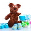 Beautiful gifts, babys bootees and bear toy isolated on white — Stock Photo