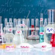 Test-tubes with various acids and other chemicals on the background of the blackboard - Photo